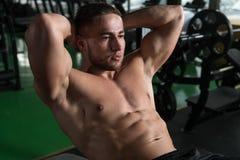 Sentar-UPS que hace masculino en un gimnasio Fotografía de archivo