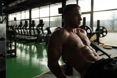 Sentar-UPS que hace masculino en un gimnasio Fotografía de archivo libre de regalías