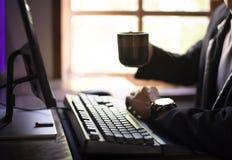 Sente-se e trabalhe-se no computador, sorva-se o caf? na manh? imagem de stock royalty free