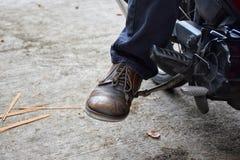 Sente-se em sua motocicleta e ligue-se o motor com a haste do começo do pé ou o acionador de partida de pontapé fotos de stock
