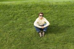 Sente-se na grama Imagem de Stock Royalty Free
