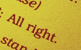 Sentence on a book paper. The sentence ` all right` on a book paper , in the background a bracket and a point , in the foreground letters , studio shot , red royalty free stock photo