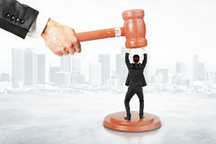 Sentence concept with businessman resists gavel at city backgrou Stock Photos
