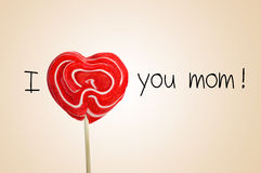 The sentence I love you mom with a heart-shaped lollipop. The sentence I love you mom with a red heart-shaped lollipop instead of the word love, on a beige Stock Image