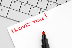 Sentence I love you written on paper. Paper with handwritten sentence I love you on a laptop keyboard Stock Images