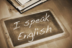 I speak english. Sentence I speak english written with chalk on a blackboard, on a table with books Stock Photos