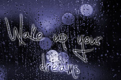 Sentence Wake up your dreams written on a wet glass. Night city life through windscreen: darkness and rain Stock Photo