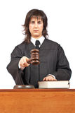 Sentencing. Angry female judge pointing at you in a courtroom. Focus on gavel and shallow depth of field royalty free stock photo