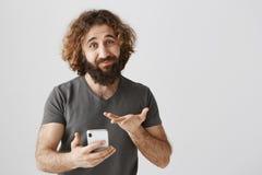 Sentez-vous désolé pour ceux qui n'ont pas acheté ce téléphone encore Portrait de l'homme de accentuation amical tenant le smartp Photos stock