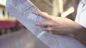 Sentido fêmea novo feliz e vista no mapa de lugar no estação de caminhos-de-ferro antes do curso vídeos de arquivo
