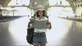 Sentido fêmea novo feliz e vista no mapa de lugar no estação de caminhos-de-ferro antes do curso video estoque