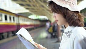 Sentido fêmea novo feliz e vista no mapa de lugar no estação de caminhos-de-ferro antes do curso filme