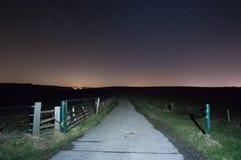 Sentier d'exploitation sous le ciel étoilé avec doyen est Village Image stock