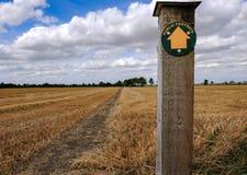 Sentier piéton vide vu près d'un champ moissonné en été, montrant une direction de sentier piéton images stock