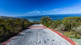 Sentiero per pedoni della pietra della strada privata del veicolo verso l'orizzonte dell'oceano immagini stock libere da diritti