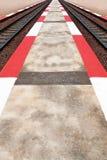 Sentiero per pedoni della striscia di bianco & di rosso fra la ferrovia fotografie stock