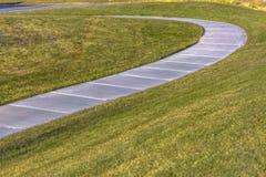 Sentiero per pedoni pavimentato che curva attraverso il terreno erboso osservato un giorno soleggiato immagini stock libere da diritti