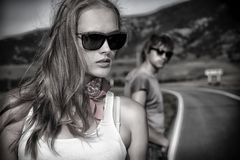 Sentiment. Couple of modern young people posing on a road over picturesque landscape Stock Image