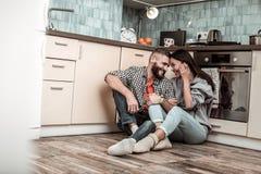 Sentiment aimant de couples mémorable tout en se reposant dans la cuisine photographie stock