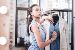 Sentiment assidu de styliste occupé tout en pensant aux équipements pour ses clients photographie stock libre de droits