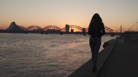 Sentiment de jeune femme sûr pendant une promenade de mode de vie le long de la dvina occidentale de rivière à un coucher du s banque de vidéos