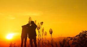 Sentiment de l'adolescence de silhouette de coucher du soleil heureux Images stock