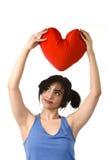 Sentiment heureux de sourire de belle femme dans l'amour tenant l'oreiller rouge de forme de coeur Image libre de droits