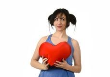 Sentiment heureux de sourire de belle femme dans l'amour tenant l'oreiller rouge de forme de coeur Image stock