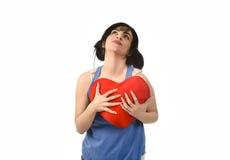 Sentiment heureux de sourire de belle femme dans l'amour tenant l'oreiller rouge de forme de coeur Photographie stock libre de droits