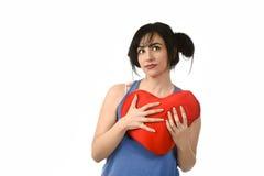 Sentiment heureux de sourire de belle femme dans l'amour tenant l'oreiller rouge de forme de coeur Photo libre de droits