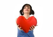 Sentiment heureux de sourire de belle femme dans l'amour tenant l'oreiller rouge de forme de coeur Photos libres de droits