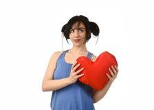 Sentiment heureux de sourire de belle femme dans l'amour tenant l'oreiller rouge de forme de coeur Images stock