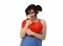 Sentiment heureux de sourire de femme attirante et belle dans l'amour tenant l'oreiller rouge de forme de coeur Photographie stock