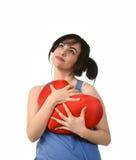Sentiment heureux de sourire de femme attirante et belle dans l'amour tenant l'oreiller rouge de forme de coeur Image stock