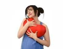Sentiment heureux de sourire de femme attirante et belle dans l'amour tenant l'oreiller rouge de forme de coeur Photo libre de droits