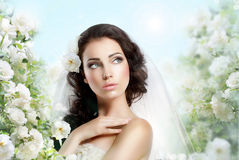 Sentiment. Perfect Exquisite Woman with Flowers over Vernal Floral Background. Lovely Bride with Flowers over Spring Background posing stock photo