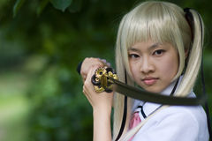 Sentimental samurai girl. A sentimental girl handling a long samurai sword Royalty Free Stock Image