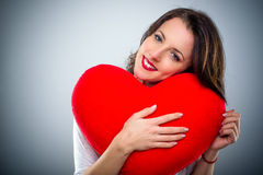Sentimental young woman in love. Hugging a large red heart with a tender smile in a Valentines Day concept Stock Photography