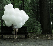 Sentimentality. Nostalgia. Lonely Woman with Air Balloons sitting on Bench in the Park Stock Photo