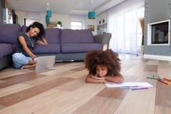 Sentimento afro-americano virado da menina furado quando mãe que usa o portátil fotos de stock