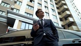 Sentimento alegre feliz, smartphone do homem de negócios da terra arrendada, projeto rentável imagem de stock
