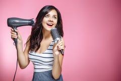 Sentimento bonito da jovem mulher feliz e que canta ao usar um hairdryer e uma escova de cabelo no fundo cor-de-rosa foto de stock