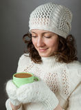 Sentimento bonito da menina frio e terra arrendada um o copo da bebida quente Foto de Stock Royalty Free