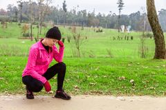 Sentimento da jovem mulher lightheaded ou com dor de cabeça após o trem em um dia de inverno frio na trilha do treinamento de um  Foto de Stock