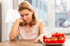 Sentimento da mulher incômodo tendo a alergia aos tomates imagem de stock