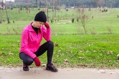 Sentimento do atleta da jovem mulher lightheaded ou com dor de cabeça Fotografia de Stock Royalty Free