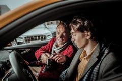 Sentimento generoso do pai excitado apresentando chaves do carro a seu filho imagem de stock royalty free