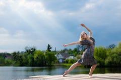 Sentimento livre: retrato da menina de dança loura bonita nova da senhora com raios de iluminação de queda do sol do céu azul no  Fotografia de Stock Royalty Free