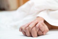 Sentimento nas mãos dos pares da paixão que têm o sexo dois pares dos amantes que guardam as mãos sob as folhas brancas gerais na foto de stock