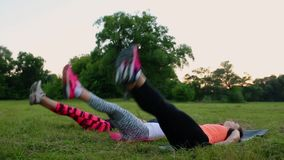 Sentindo suas meninas do Abs Grupo de povos atléticos novos no sportswear que faz exercícios físicos na grama verde no verão vídeos de arquivo